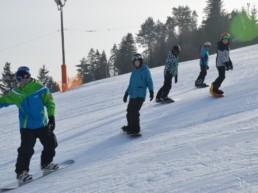Młodzież w trakcie snowboardowego obozu zimowego.