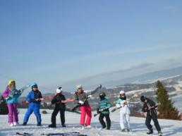 Dzici w trakcie nauki jazdy na nartach i snowboardzie.